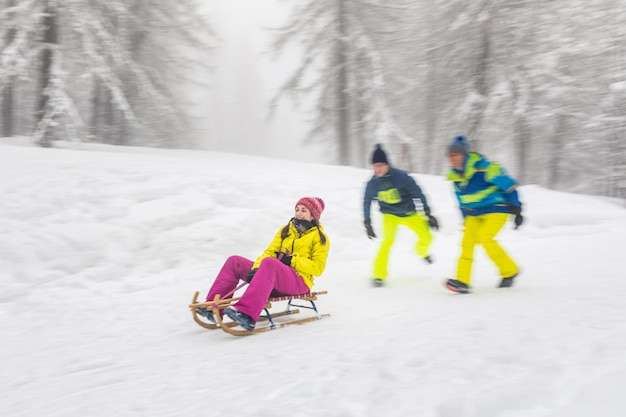 Friends having fun on the snow sliding with a little sled