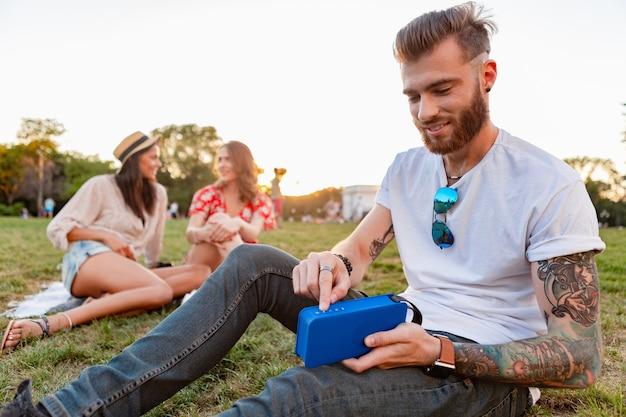 Amici che si divertono insieme nel parco sorridendo ascoltando musica su altoparlanti wireless