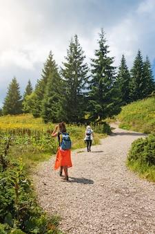 友達が一緒に楽しんで、女性が山でハイキングします。幸せな旅行者、目標、成功、自由および達成の概念。カルパティア山脈、ホベルラ、ウクライナ。