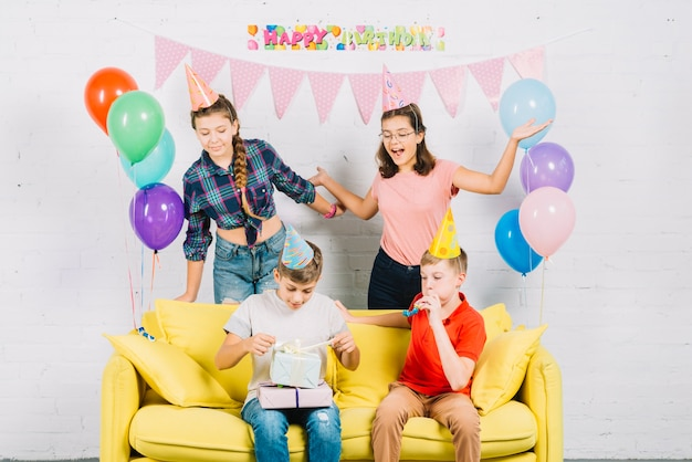Friends having fun while boy sitting on sofa unwrapping birthday gifts at home