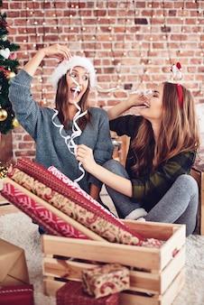Amici che si divertono mentre preparano le decorazioni natalizie