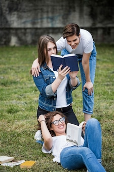 Friends having fun with books in park