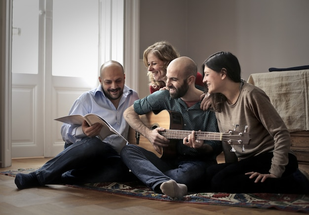 Friends having fun with a guitar at home