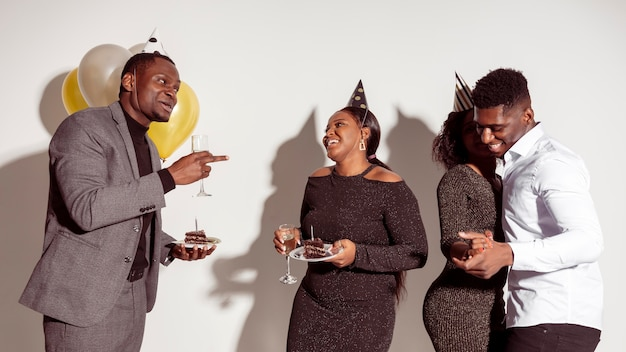 Amici che si divertono e mangiano la torta