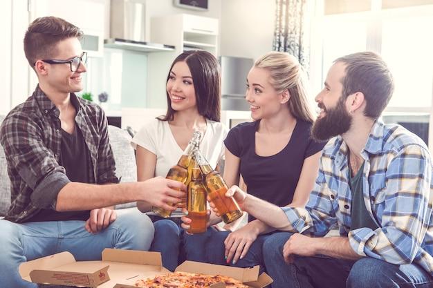 ピザを食べて屋内で一緒にパーティーをしている友達