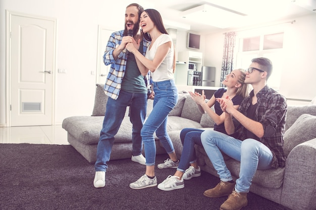 Friends having party together indoors singing karaoke