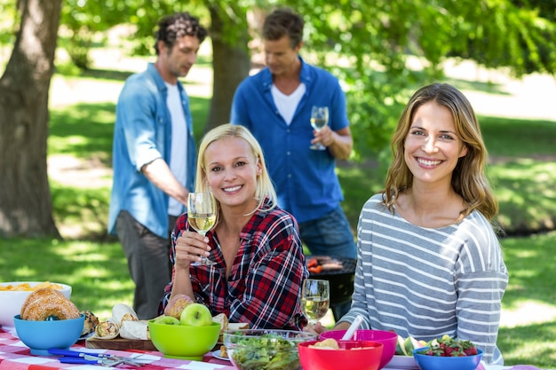 Friends having a picnic with wine and barbecue