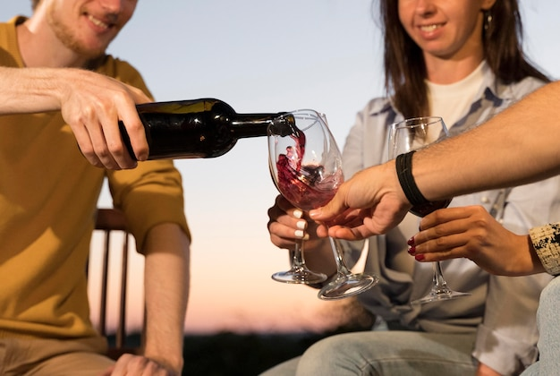 Friends having some wine while outdoors during dusk