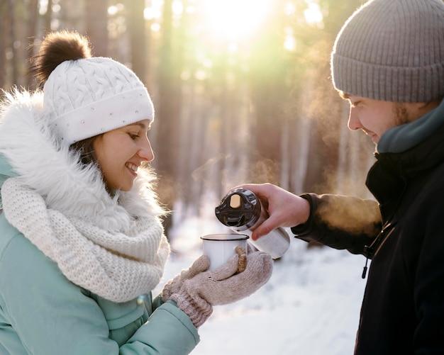 冬に屋外でお茶を飲む友達