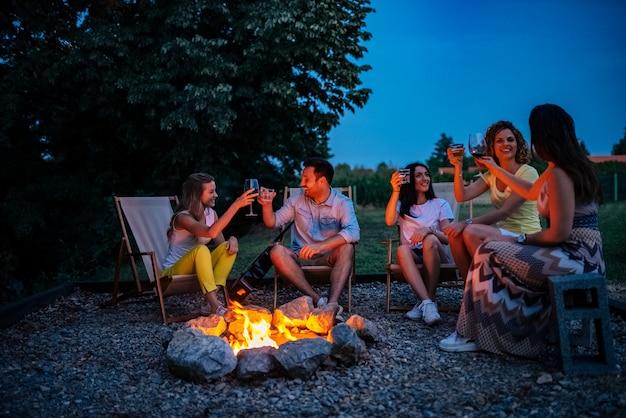 Friends having a toast around the bonfire.