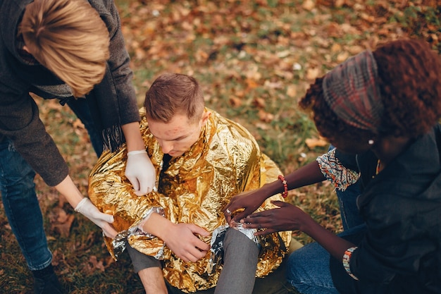 友達が男を助けます。地面に座っている負傷した少年。公園で応急処置を提供します。
