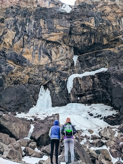 Friends on a hike in the mountains enjoy the view of the frozen waterfall in winter