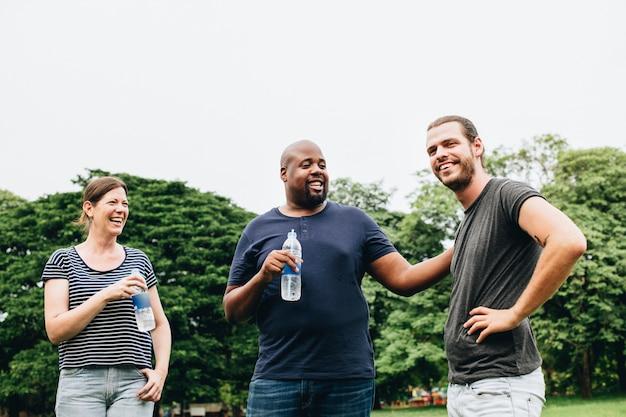 Друзья держат бутылку воды и общаются в парке