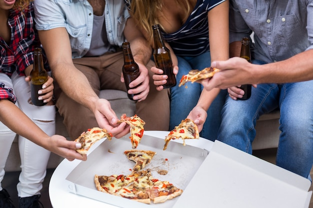 Friends holding beer while eating pizza at home