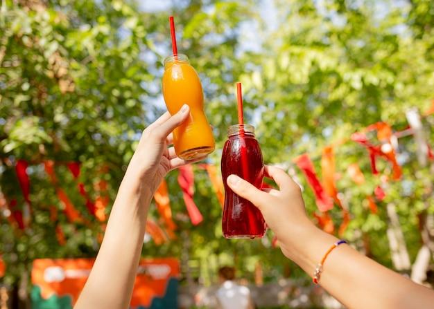 Amici che tengono le bottiglie di succo di frutta fresco nel parco