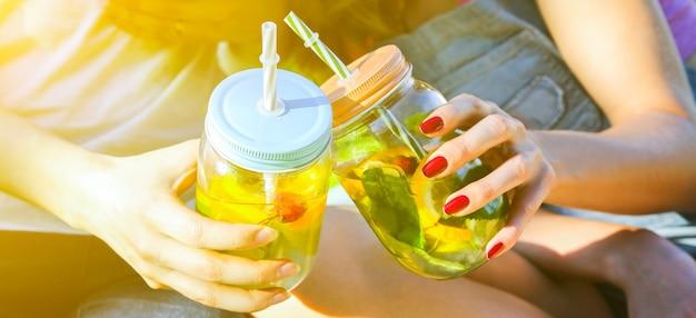 ストローの入った瓶に新鮮なレモネードを持っている友達。飲み物と流行に敏感な夏のパーティー。健康的なビーガンライフスタイル。自然の中で環境にやさしい。ガラスにミントが入ったレモン、オレンジ、ベリー。