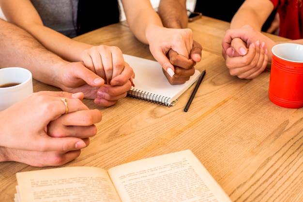 Friends holding hands near stationery and coffee cups over wooden desk