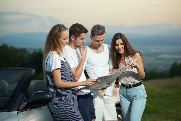 Friends holding map and planning journey by cabriolet.