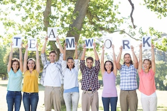 Friends holding teamwork signs in the park