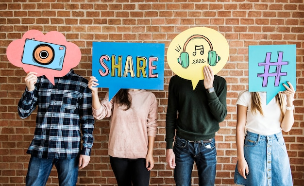 Friends holding up thought bubbles with social media concept icons