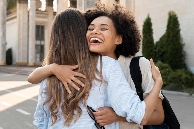 屋外でお互いを見た後に抱き合う友達