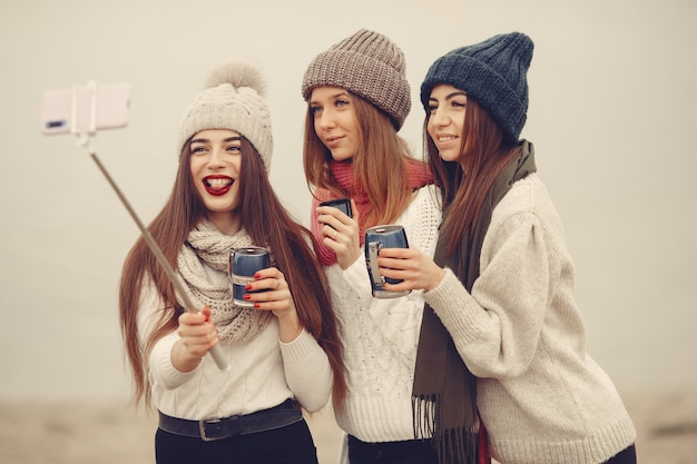 Друзья в зимнем парке. девушки в вязаных шапках. женщины с термосом и чаем.