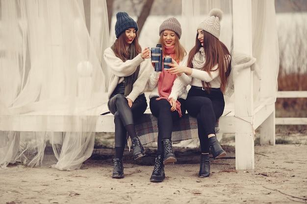 冬の公園の友達。ニット帽子をかぶった女の子。魔法瓶とお茶の女性。