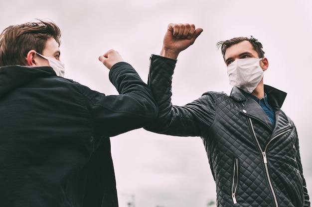保護マスクをかぶった友達がお互いに挨拶します。