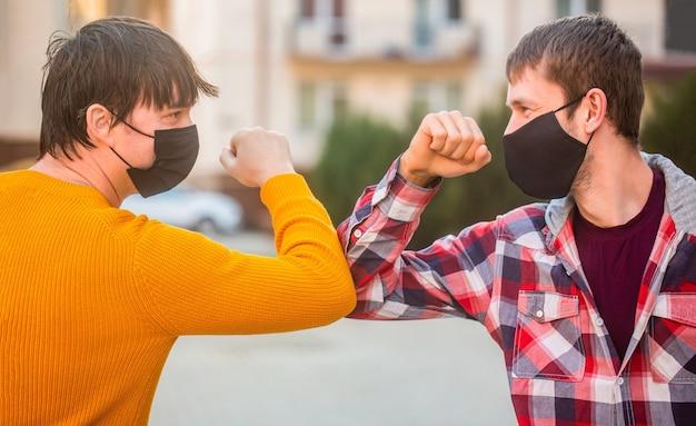 彼の顔に保護用マスクを付けた友人は、検疫で肘を迎えます。肘のバンプ。コロナウイルス、病気、感染症、検疫、医療用マスク、covid-19。友達の医療用マスク。ひじがぶつかる。