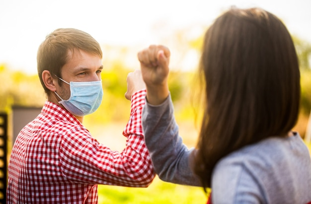 彼の顔に保護用マスクを付けた友人は、検疫で肘を迎えます。肘のバンプ。コロナウイルス、病気、検疫、医療用マスク、covid19。肘で挨拶するカップル。ひじがぶつかる。