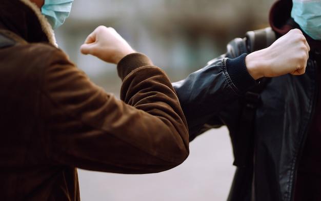 彼の顔に保護用医療マスクを付けた友人が肘に挨拶する