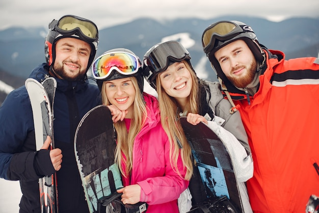 スノーボードスーツを着た友達。スノーボードで山の上のスポーツの人々。地平線上にスキーを持っている人。スポーツの概念