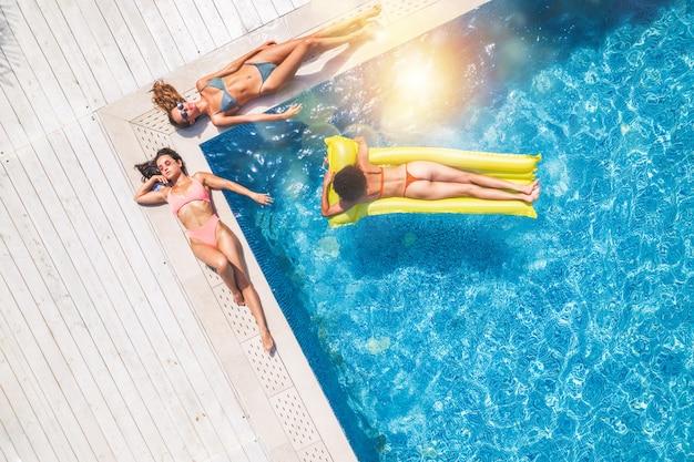 수영장에서 선베드에서 선탠하는 수영복을 입은 친구들