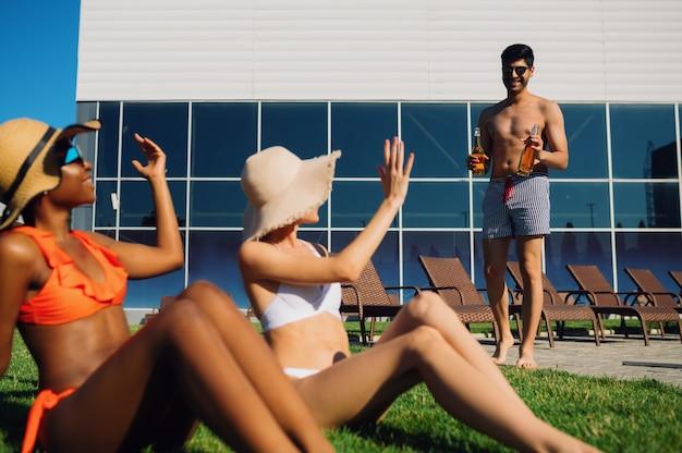 수영복을 입은 친구들은 수영장 근처 잔디에서 휴식을 취합니다.