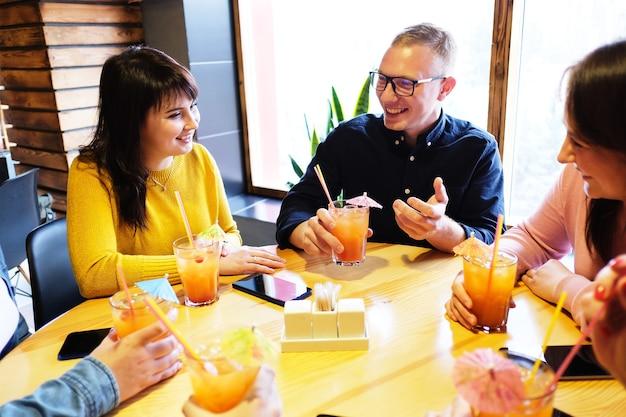 Друзья в баре пьют коктейль, разговаривают и смеются