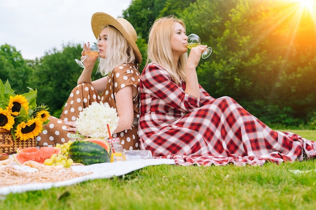 Friends is making picnic outdoor laughing girls sitting on white knit picnic blanket drinking wine h...