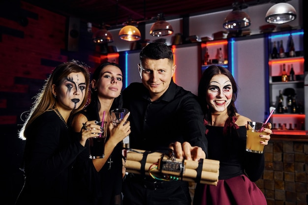 Friends is on the thematic halloween party in scary makeup and costumes and bomb in hands.