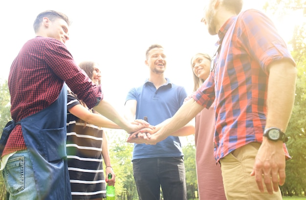 自然の中でバーベキューをしている間、友達が手を組みます。