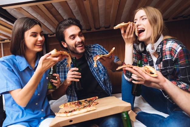 Friends laugh, hold pizza slices and eating.
