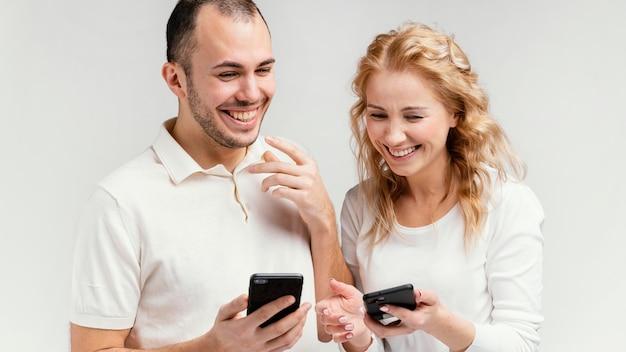 Amici che ridono e usano i cellulari