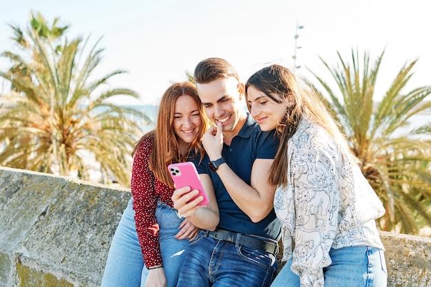 携帯電話で笑っている友達