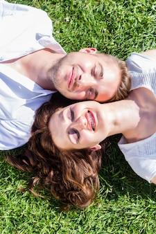 Friends laying side by side on park lawn enjoying sun