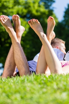 Friends laying  with crossed legs in park