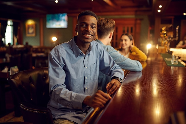Friends leisures at the counter in bar, nightlife. group of people relax in pub, night lifestyle, friendship, event celebration