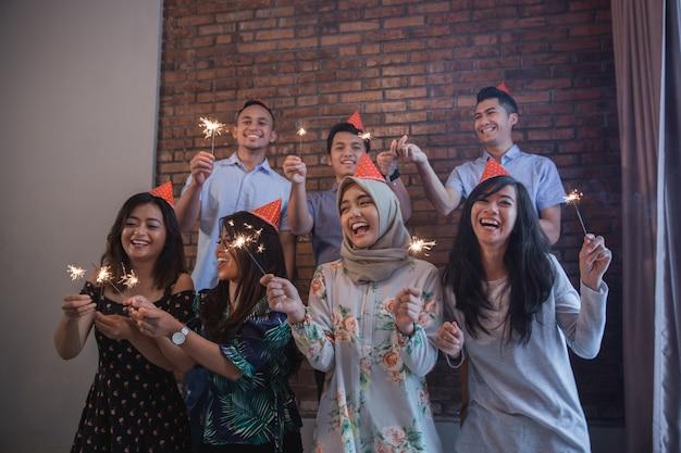 Friends lighting sparklers together. celebrating
