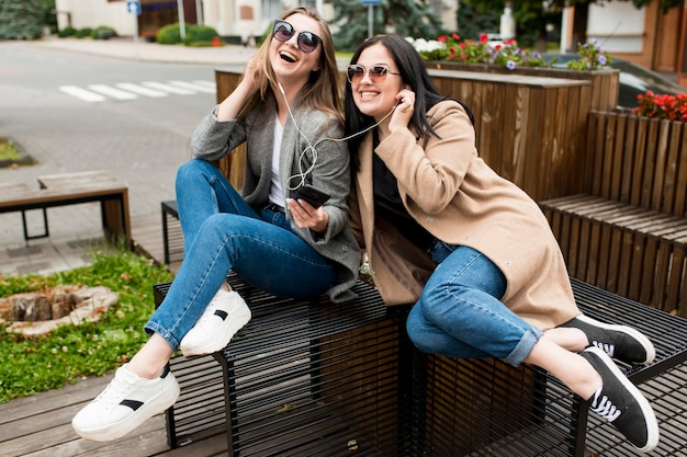 Друзья слушают музыку через наушники на улице
