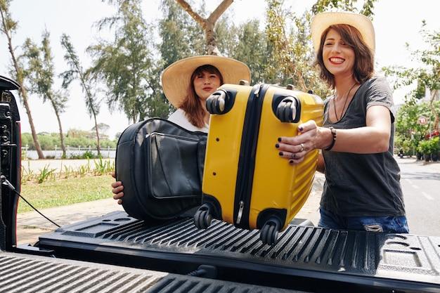 Друзья, загружающие грузовик с чемоданами