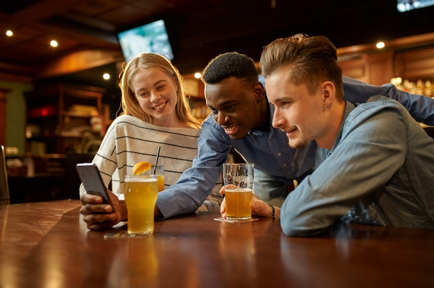 Друзья смотрят фотографии в телефоне и веселятся за столиком в баре. группа людей отдыхает в пабе, ночной образ жизни, дружба, празднование события