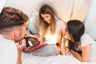 Friends looking at woman reading book with flashlight on bed