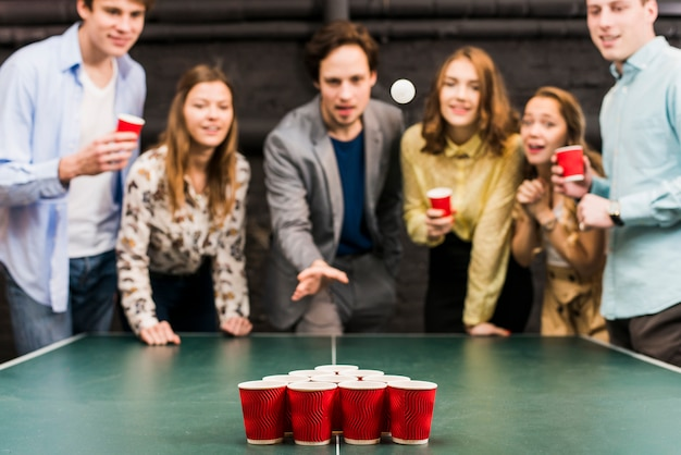 Friends looking at ball while man playing beer pong in bar